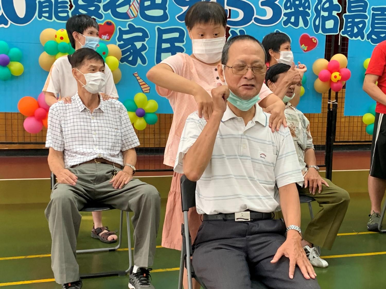 無障礙之家辦理父親節活動,憨兒為父親按摩肩頸,放鬆筋絡。