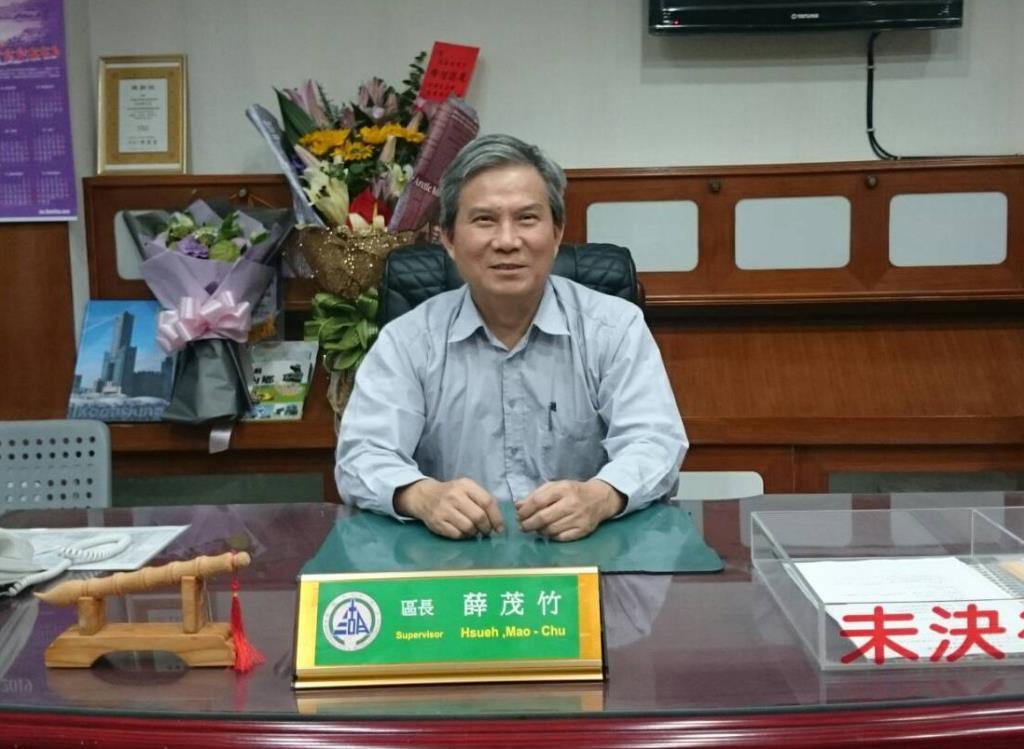 區長坐於辦公桌前和桌後背景裝飾之照片